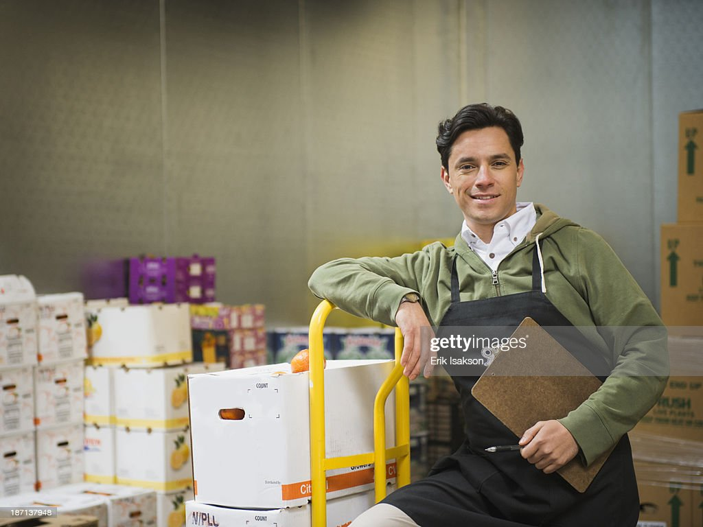 Hispanic worker carting boxes in walk-in freezer : Stock Photo