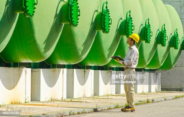 Hispanic worker checking tanks