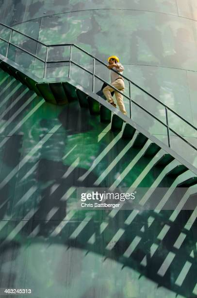 Hispanic worker climbing water tower
