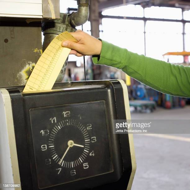 Hispanic worker clocking in in factory