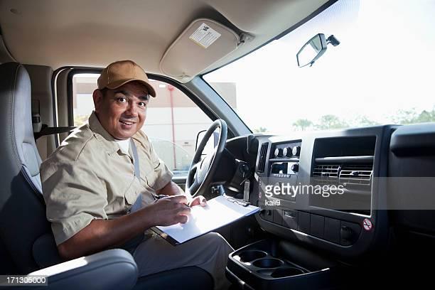 Hispanic worker driving van