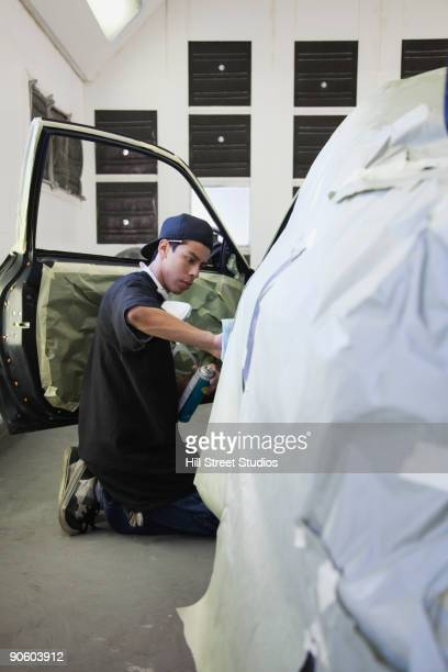 Hispanic worker fixing car in auto body shop
