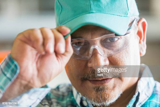 Hispanic worker in safety glasses, cap and plaid shirt