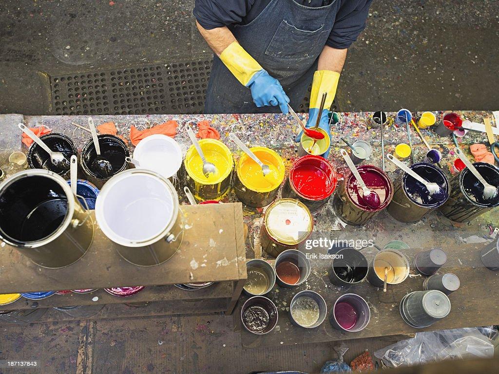 Hispanic worker mixing paint in workshop