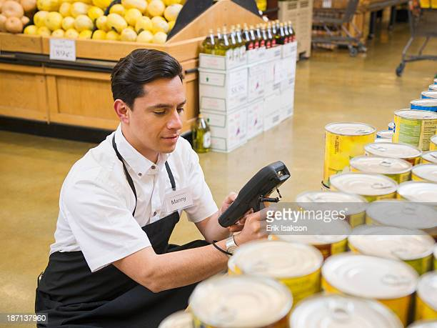 Hispanic worker scanning items in grocery store