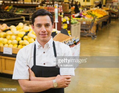 Hispanic worker smiling in grocery store