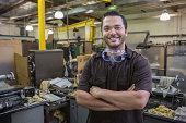 Hispanic worker smiling in repair shop