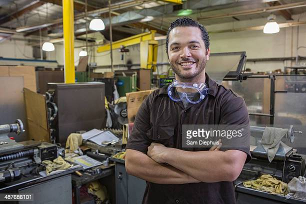 Hispanic worker smiling in repair shop