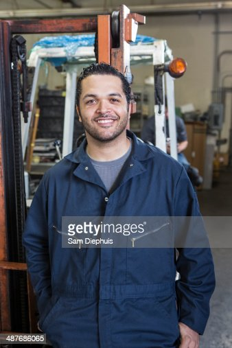 Hispanic worker smiling in warehouse
