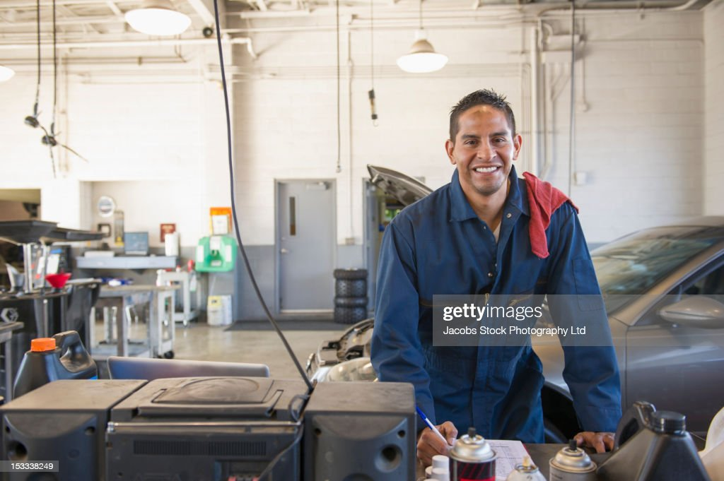Hispanic worker standing in auto repair shop