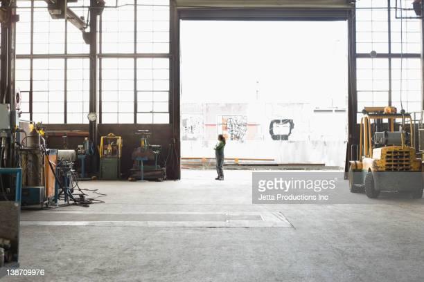 Hispanic worker standing in warehouse doorway