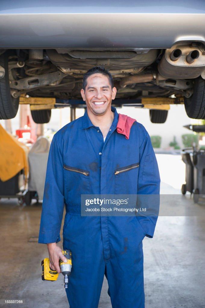 Hispanic worker standing underneath car