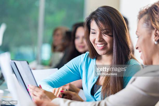 Hispanic young businesswoman looking at paperwork during business conference seminar