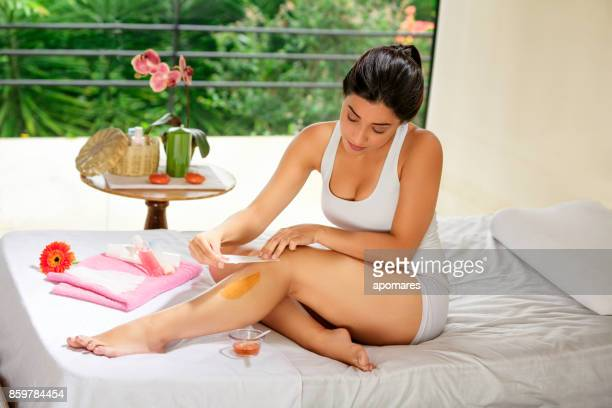Hisoire jeune femme à l'aide de cire d'épilation sur les jambes