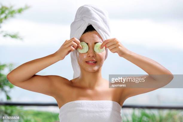 Hisoire jeune femme avec CREME sur des tranches de concombre et de visage sur ses yeux