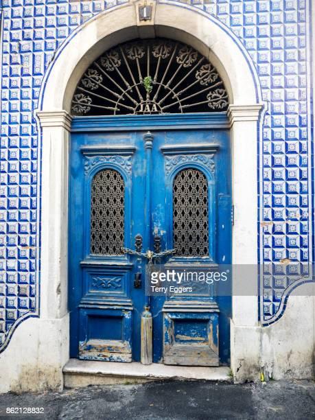 Historic Alfama district, blue door with chain lock. Hand of Fatima symbol on door knockers.