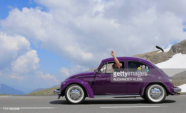 Historic car enthusiasts drive a vintage Volkswagen Beetle during a classic car excursion on the Grossglockner high alpine road at the Hochtor pass...
