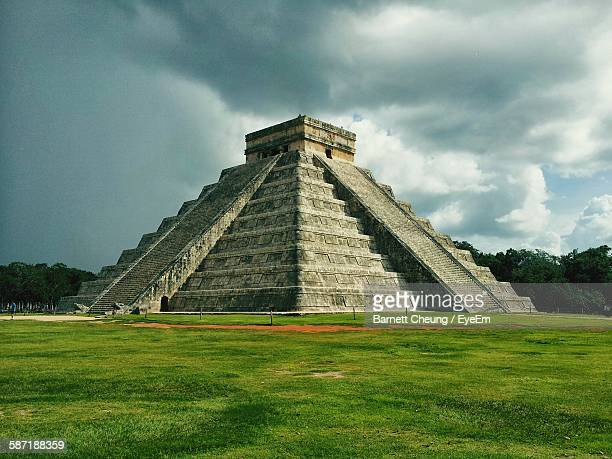 Historic Chichen Itza On Green Field Against Sky