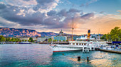 Panoramic view of the historic city center of Geneva with traditional paddle steamer boat on Lake Geneva in beautiful golden evening light at sunset with blue sky and clouds in summer, Switzerland.