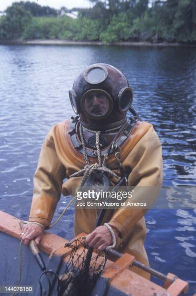 Historic Greek sponge diver in antique diving suit dives for sponges in Tarpon Springs FL