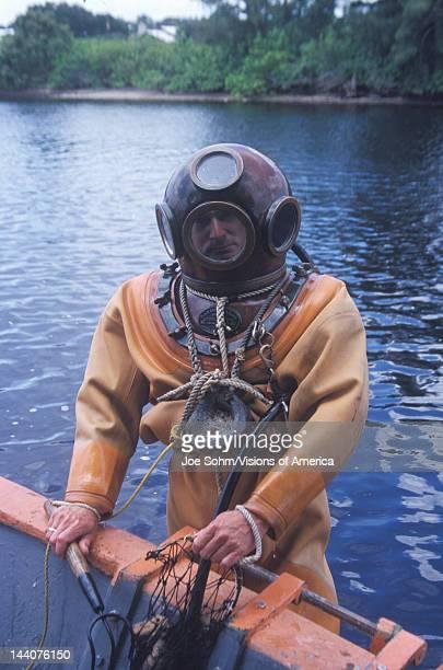 Historic Greek sponge diver in antique diving suit dives for sponges in Tarpon Springs FL