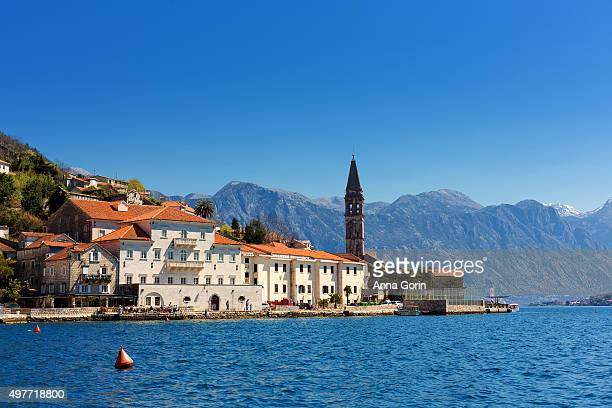 Historic Perast shoreline and bell tower in Montenegro viewed across Bay of Kotor from shuttle boat