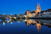 Historic Regensburg illuminated at dusk.