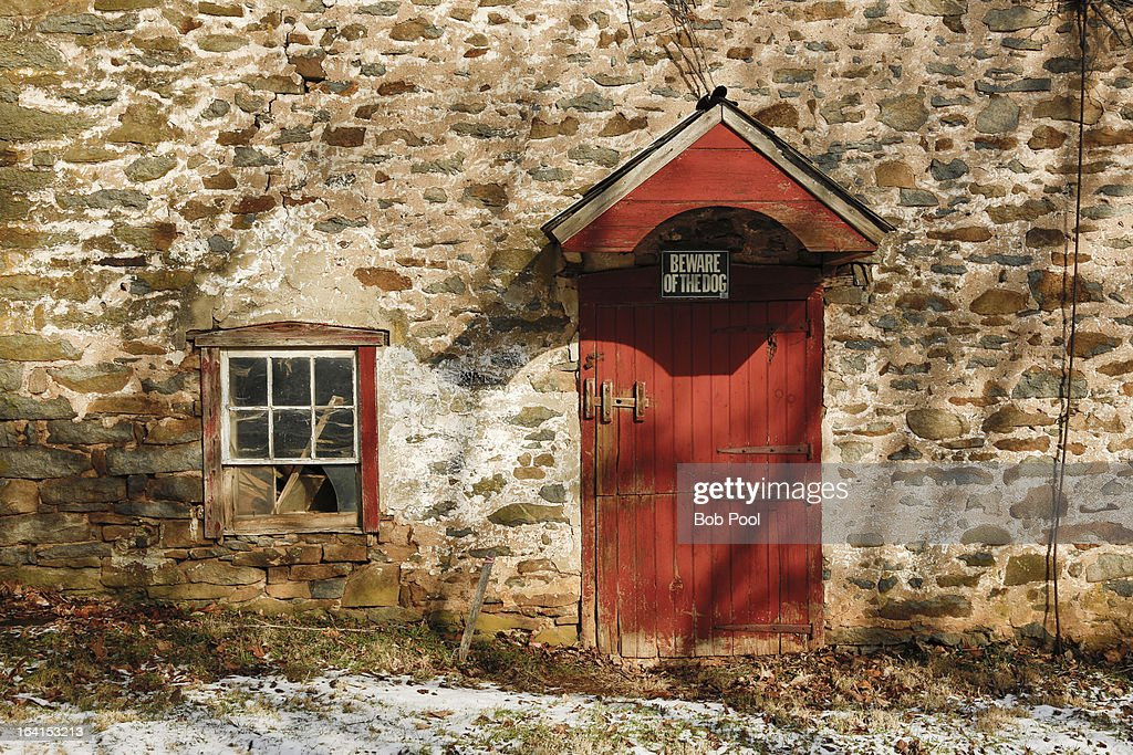Historic stone barn with red door : Stock Photo