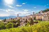 Panoramic view of the historic town of Assisi on a beautiful sunny day with blue sky and clouds in summer, Umbria, Italy.