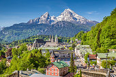 Historic town of Berchtesgaden with famous Watzmann mountain in the background on a sunny day with blue sky and clouds in springtime, Nationalpark Berchtesgadener Land, Upper Bavaria, Germany.