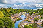 Aerial view of the historic town of Dinan with Rance river with dramatic cloudscape, Cotes-d'Armor department, Bretagne, northwestern France.