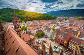 Aerial view of the historic city center of Freiburg im Breisgau from famous Freiburger Minster in beautiful evening light at sunset with blue sky and clouds in summer, Baden-Wurttemberg, Germany.