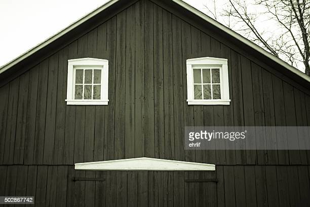 Century old barn with an abstract happy face on the facade. Horizontal orientation in black and white.
