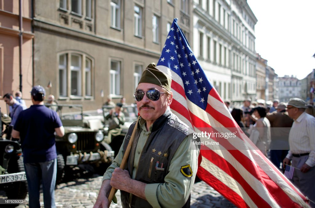 A history enthusiast dressed in WWII US army uniform carries the flag of USA during the ''Convoy of Liberty'' event on April 26, 2013 in Prague, Czech Republic. 'Convoy of Liberty' commemorates when in 1945 the western part of the Czech Republic was liberated by the US Army from Nazi oppression. The convoy's route begins in Prague tomorrow and makes its first stop in front of the US Embassy, where it will be met by the Czech Army Military Band.