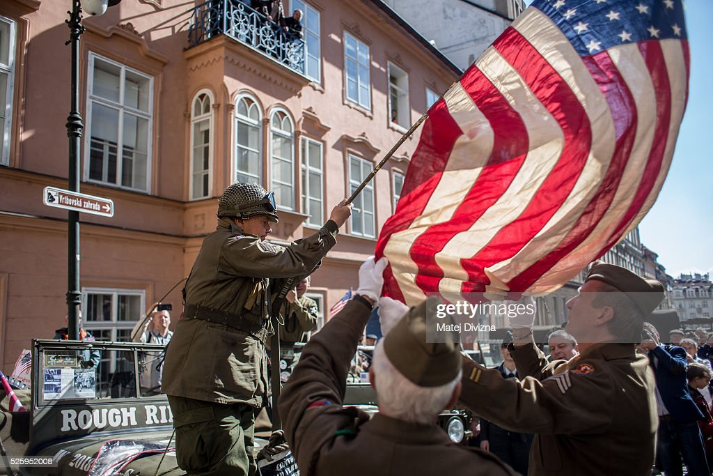 History enthusiasts dressed in WWII US army uniform fasten the American flag during the 'Convoy of Liberty' event on April 29, 2016 in Prague, Czech Republic. The 'Convoy of Liberty' commemorates the 71st anniversarry of the liberation of the western part of the Czech Republic by the US Army from Nazi oppression in 1945. The convoy's route begins on the bank of Vltava river in Prague and makes its first stop in front of the US Embassy, where it will be met by the Czech Army Military Band.