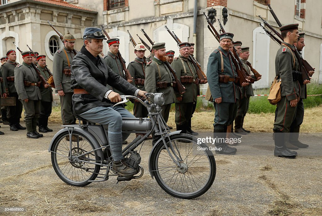 History reenactors wearing World War I German military uniforms stand at attention as man riding a World War I-era motorcycle drives past at their campsite prior to a parade on May 27, 2016 in Verdun, France. The governments of France and Germany will commemorate the 100th anniversary of the World War I Battle of Verdun with ceremonies this coming Sunday. Approximately 300,000 soldiers lost their lives in the 10-month campaign that was among the most grueling battles of World War I.