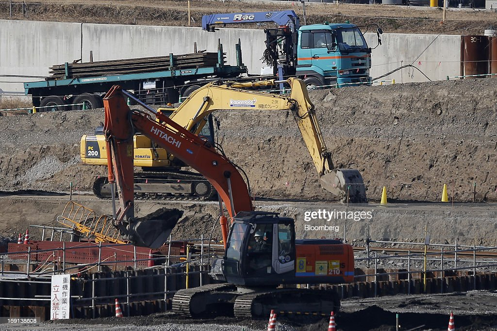A Hitachi Construction Machinery Co. excavator, front, and a Komatsu Ltd. excavator operate on a construction site in Tokyo, Japan, on Tuesday, Jan. 8, 2013. Prime Minister Shinzo Abe aims to compile Japan's economic stimulus package on Jan. 11, and seeks to have new economic growth strategy by mid-year. Photographer: Kiyoshi Ota/Bloomberg via Getty Images
