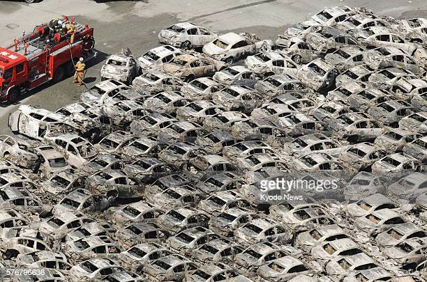 Hitachi Japan Photo taken from a Kyodo News helicopter on March 12 shows passenger cars which were burned in a fire that broke out following the...