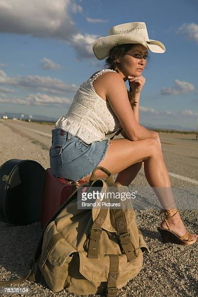 Hitchhiker sitting on side of the road