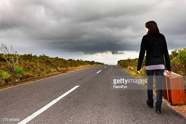 Hitchhiker walks away down deserted road under stormy sky