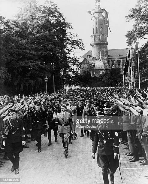 Hitler is surrounded by cronies and cheering crowds as he leaves the castle at Weimar after attending the tenth anniversary celebration of the first...