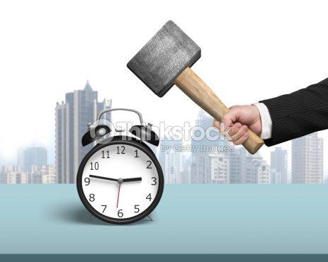 Golpear despertador con martillo en la tabla : Foto de stock