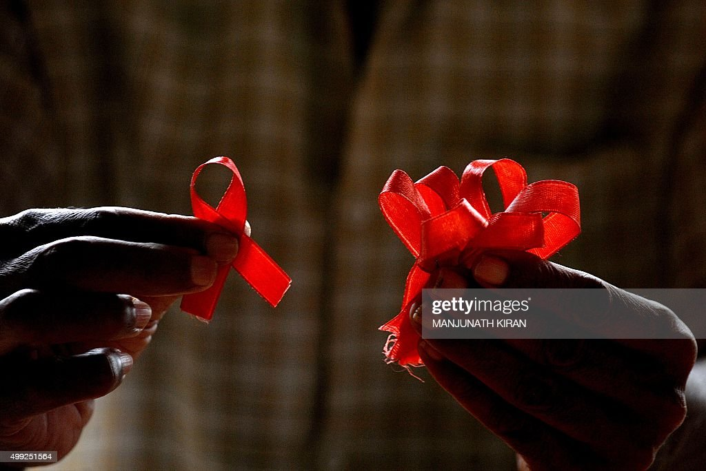 A HIVpositive person from the Support and Care Centre of the Sumanahalli Society prepares 'red ribbons' on the eve of World Aids Day in Bangalore on...