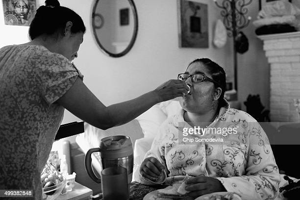 HIVpositive Shana ReynoldsFairley gets help taking her pain medication from Joseph's House nurses aide Tsering Sangmo August 6 2013 in Washington DC...