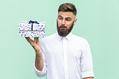 Hmm what is it! Bearded man looking at gift box and want too open. Light green background. Studio shot