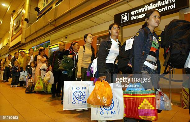 Hmong refugees from Wat Tham Krabok refugee camp stand in line waiting to pass through immigration en route to the United States at Bangkok...