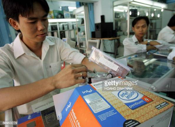 A saleman shows off an Intel processor to a customer inside a computer shop in downtown Ho Chi Minh City 28 Feburary 2006 US giant chipmaker Intel...