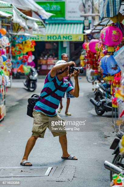 Ho Chi Minh - Viet Nam, August 18, 2014: The photographer is taking photos at Luong Nhu Hoc street.