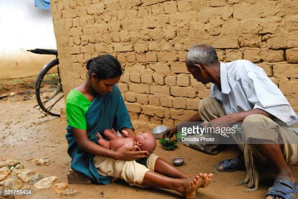Ho tribes mother with baby and barber, Chakradharpur, Jharkhand, India