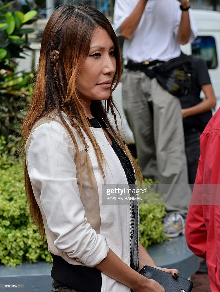 Ho Yeow Sun, pop-singer wife of City Harvest Church founder Kong Hee (not in picture), waits to get into the car for lunch break outside the subordinate courts in Singapore on September 9, 2013. Trial continues for the leaders of a Singapore-based Christian church accused of embezzling millions of dollars to finance the singing career of the pastor's wife.